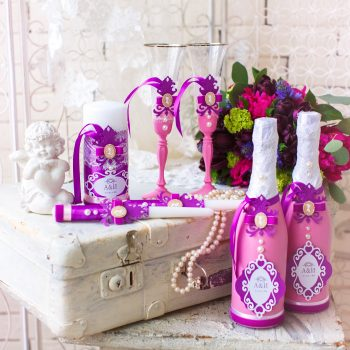 Wedding accessories for the morning of the bride in pink . Wedding bouquet of the bride. Decorated champagne glasses, bottle of champagne, pearl necklace and candles.